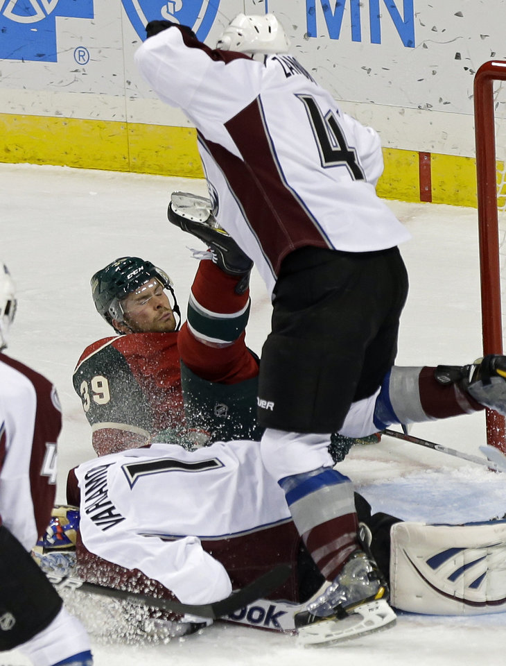 Colorado Avalanche's Greg Zanon, right, sends Minnesota Wild's Nate Prosser  toppling over Avalanche goalie Semyon Varlamov of Russia, bottom, in the first period of an NHL hockey game Saturday, Jan. 19, 2013 in St. Paul, Minn.  (AP Photo/Jim Mone)