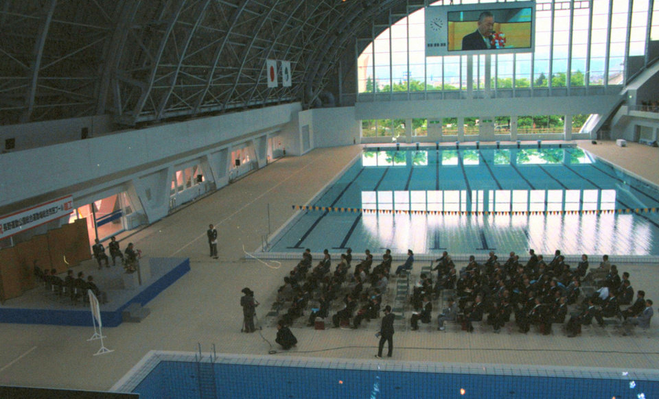 Photo - In this May 16, 1999 photo, an aquatics center is unveiled during a ceremony in Nagano, central Japan. The Aqua Wing Arena, which hosted the ice hockey events in the 1998 Winter Olympics, was converted into an aquatics center.  In Nagano, a city with a population of just 387,000, five large structures were built for the 1998 Winter Games. They are in use, but many say the venues are too big and costly to maintain for the size of the town. (AP Photo/Kyodo News) JAPAN OUT.
