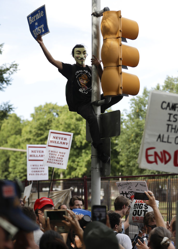 Photo - A supporter of Sen. Bernie Sanders, I-Vt., yells at delegates over fence after climbing a light pole in Franklin Delano Roosevelt Park in Philadelphia, Tuesday, July 26, 2016, during the second day of the Democratic National Convention. (AP Photo/Matt Slocum)
