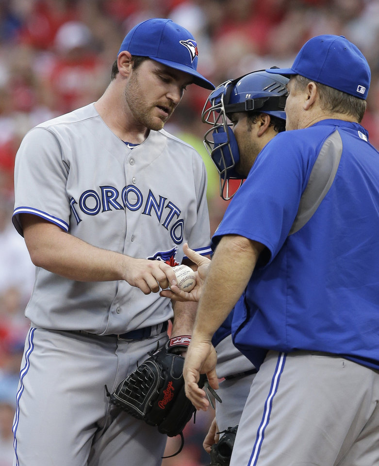 Photo - Toronto Blue Jays starting pitcher Liam Hendriks, left, is taken out by manager John Gibbons in the second inning of a baseball game against the Cincinnati Reds, Friday, June 20, 2014, in Cincinnati. (AP Photo/Al Behrman)