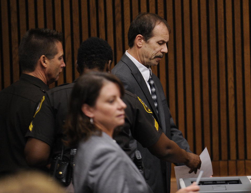 Photo - Theodore Wafer is led out of the courtroom by Wayne County Sheriff, Wednesday, Sept. 3, 2014, 2014, in Detroit, after he was sentenced to at least 17 years in prison for killing an unarmed woman on his porch. During the trial, he said he shot 19-year-old Renisha McBride because he feared for his life, but a jury rejected Wafer's claim of self-defense. (AP Photo/Detroit News, Clarence Tabb Jr.)  DETROIT FREE PRESS OUT; HUFFINGTON POST OUT, MANDATORY CREDIT