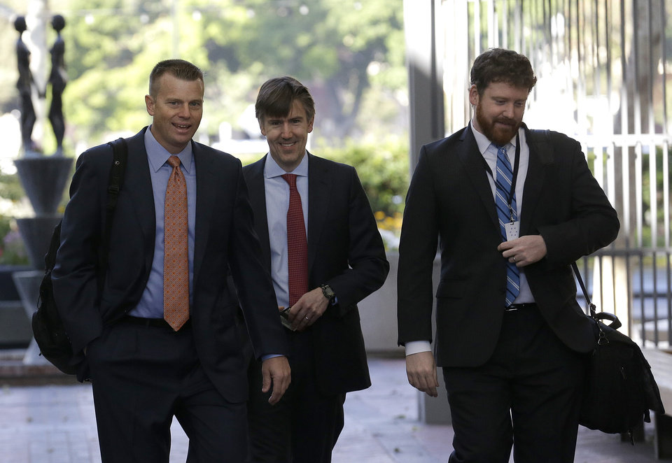 Photo - Samsung attorney David Nelson, left, walks with others to a federal courthouse in San Jose, Calif., Tuesday, April 29, 2014. The Silicon Valley court battle between Apple and Samsung is entering its final phase. Lawyers for both companies are expected to deliver closing arguments Tuesday before jurors are sent behind closed doors to determine a verdict in a closely watched trial over the ownership of smartphone technology. (AP Photo/Jeff Chiu)