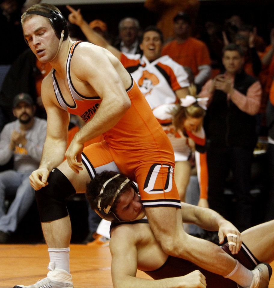 Oklahoma State 174-pound wrestler Chris Perry gets up off the matt over Oklahoma\'s Derek Geiges after Perry pinned Geiges in a wrestling dual between Oklahoma State and Oklahoma at Gallagher Iba Arena in Stillwater on Feb. 9, 2014. Photo by KT King/For the Oklahoman
