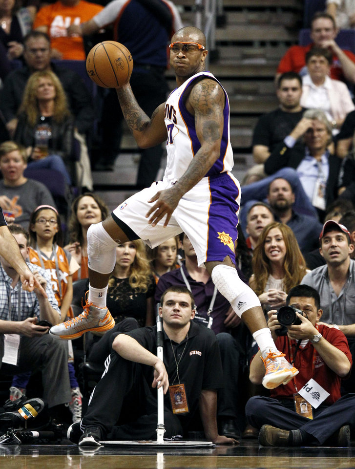 Photo -   Phoenix Suns' P.J. Tucker jumps in the air to save the ball from going out-of-bounds during the first half of an NBA basketball game against the Portland Trail Blazers, Wednesday, Nov. 21, 2012, in Phoenix. (AP Photo/Ross D. Franklin)