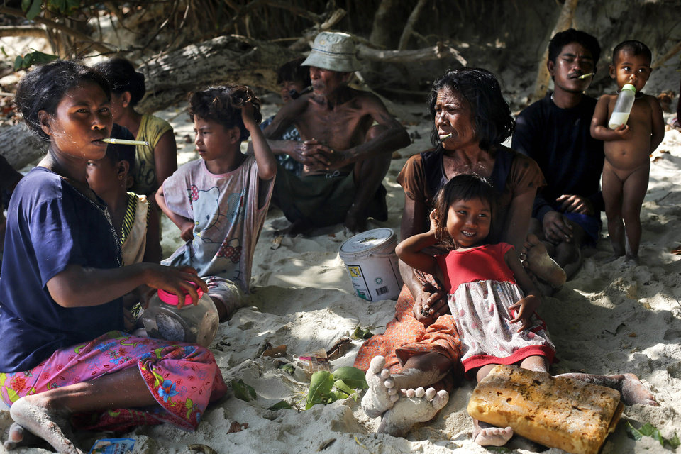 Photo - In this Sunday, Feb. 9, 2014 photo, a group of Moken families, nomads of the sea, rest in the shade of trees on Island 115 in Mergui Archipelago, Myanmar. The Moken group of several families are spending 10 days hunting for squid and whatever else they can collect before returning to their village on another island toward Myanmar's southwestern coast with a lacework of 800 islands, what is known as the Lost World. Isolated for decades by the country's former military regime and piracy, the Mergui archipelago is thought by scientists to harbor some of the world's most important marine biodiversity and looms as a lodestone for those eager to experience one of Asia's last tourism frontiers before, as many fear, it succumbs to the ravages that have befallen many of the continent's once pristine seascapes. (AP Photo/Altaf Qadri)