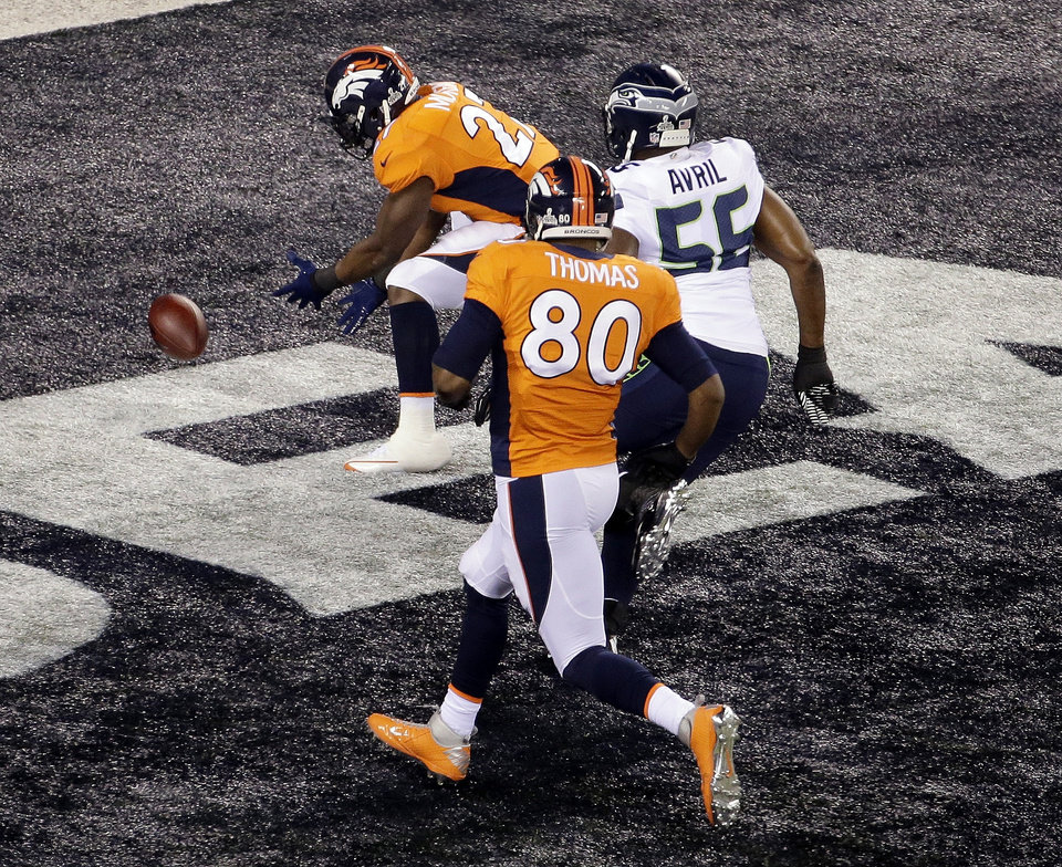 Photo - Denver Broncos' Knowshon Moreno (27) recovers the football in the end zone for a safety as Seattle Seahawks' Heath Farwell (55) and teammate Julius Thomas (80) chase him during the first half of the NFL Super Bowl XLVIII football game Sunday, Feb. 2, 2014, in East Rutherford, N.J. (AP Photo/Charlie Riedel)