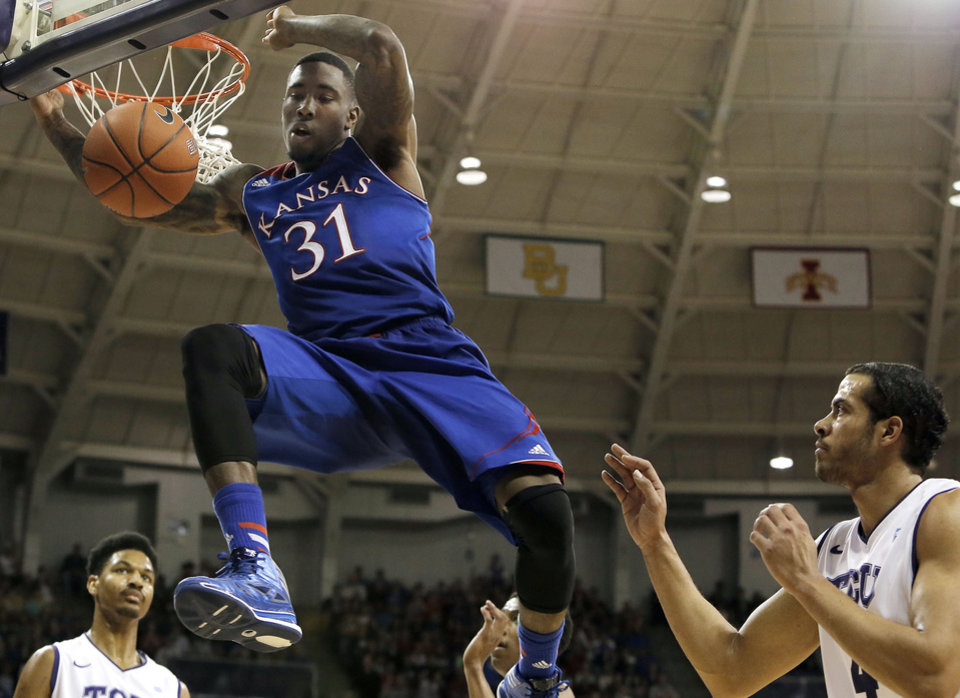 Photo - Kansas forward Jamari Traylor (31) dunks as TCU's Amric Fields, right, looks on in the first half of an NCAA college basketball game, Saturday, Jan. 25, 2014, in Fort Worth, Texas. (AP Photo/Brandon Wade)