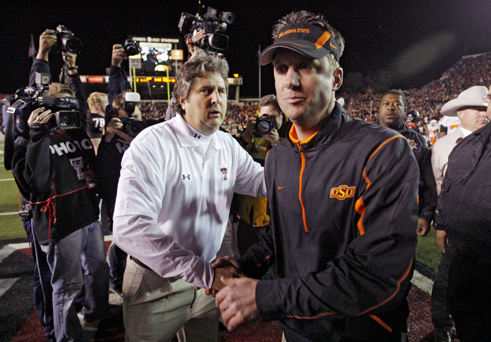 Photo - Texas Tech coach Mike Leach shakes hands with Oklahoma State coach Mike Gundy after the Cowboys 56-20 loss during the college football game between the Oklahoma State University Cowboys (OSU) and the Texas Tech Red Raiders at Jones AT&T Stadium on Saturday, Nov. 8, 2008, in Lubbock, Tex.BY CHRIS LANDSBERGER/THE OKLAHOMAN