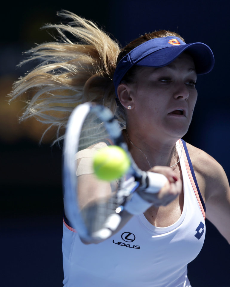 Photo - Agnieszka Radwanska of Poland makes a forehand return during her quarterfinal against Victoria Azarenka of Belarus  at the Australian Open tennis championship in Melbourne, Australia, Wednesday, Jan. 22, 2014.(AP Photo/Rick Rycroft)