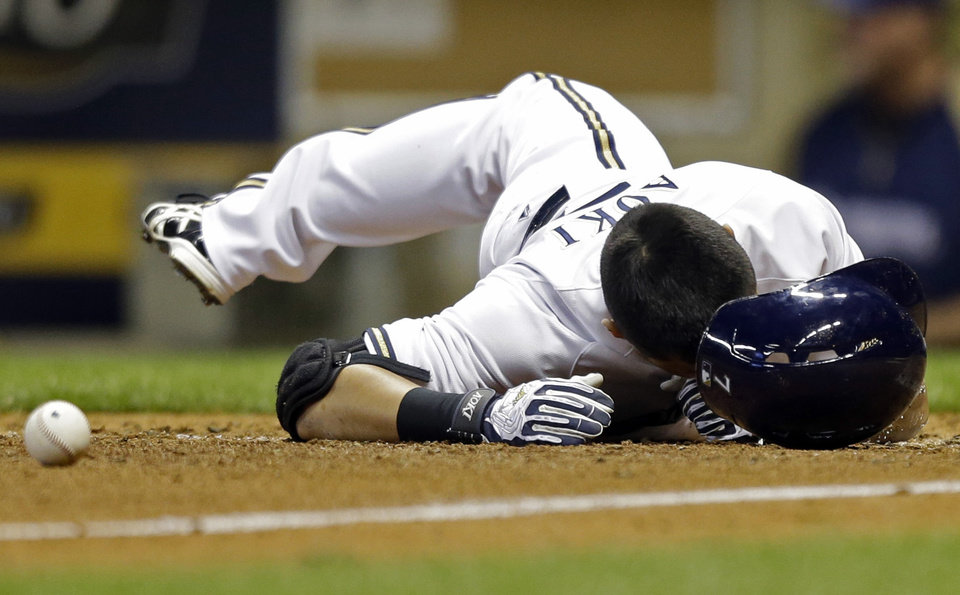 Photo - Milwaukee Brewers' Norichika Aoki is hit with a pitch from San Diego Padres' Sean O' Sullivan during the seventh inning of a baseball game on Wednesday, July 24, 2013, in Milwaukee. (AP Photo/Jeffrey Phelps)