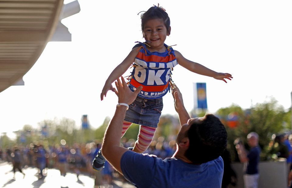 Photo - Victor Gonzalez, of Yukon, tosses his daughter Audrina Gonzalez, 3, into the air outside the arena before Game 2 in the second round of the NBA playoffs between the Oklahoma City Thunder and the Memphis Grizzlies at Chesapeake Energy Arena in Oklahoma City, Tuesday, May 7, 2013. Photo by Bryan Terry, The Oklahoman