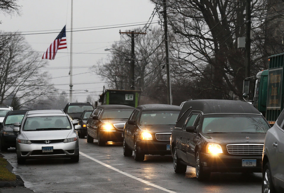Photo - A hearse and family limousines for six-year-old shooting victim Jack Pinto rolls past a flag at half staff as the funeral procession heads through the historic district in Newtown, Conn., Monday, Dec. 17, 2012. A gunman opened fire on Friday at Sandy Hook Elementary School in the town, killing 26 people, including 20 children before killing himself. (AP Photo/Charles Krupa) ORG XMIT: CTCK111