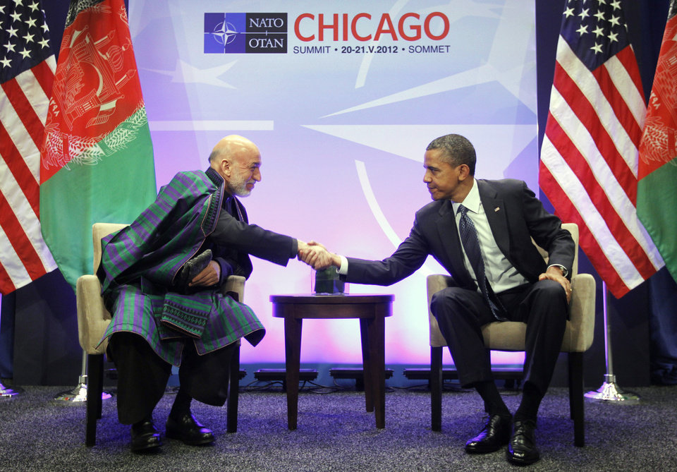 President Barack Obama, right, shakes hands with with Afghan President Hamid Karzai, left, during their meeting at the NATO Summit in Chicago, Sunday, May 20, 2012. With Obama, Karzai thanked Americans for the help their 'taxpayer money' has done in Afghanistan. (AP Photo/Pablo Martinez Monsivais)