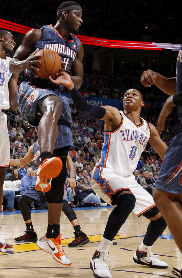 Charlotte's Kwame Brown (54) grabs a rebound in front of Oklahoma City's Russell Westbrook (0) during the NBA basketball game between the Oklahoma City Thunder and the Charlotte Bobcats at the Oklahoma City Arena, Friday, March 18, 2011. Photo by Bryan Terry, The Oklahoman