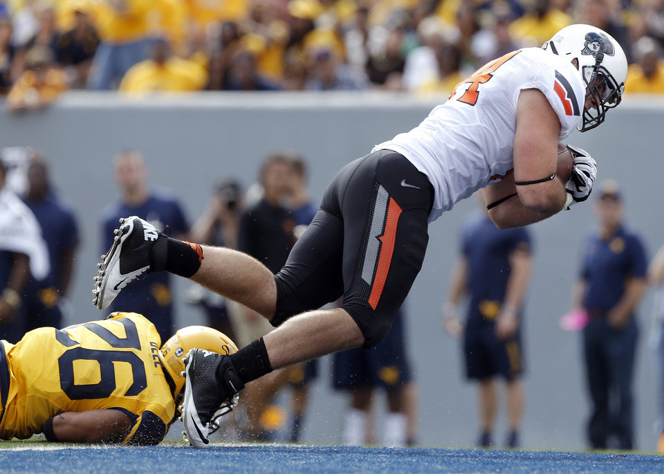 Photo - Oklahoma State's Jeremy Seaton (44) leaps into the end zone for a touchdown in front of West Virginia's Travis Bell (26) during the second half of a college football game between the Oklahoma State University and West Virginia University on Mountaineer Field at Milan Puskar Stadium in Morgantown, W. Va.,   Saturday, Sept. 28, 2013. Photo by Sarah Phipps, The Oklahoman