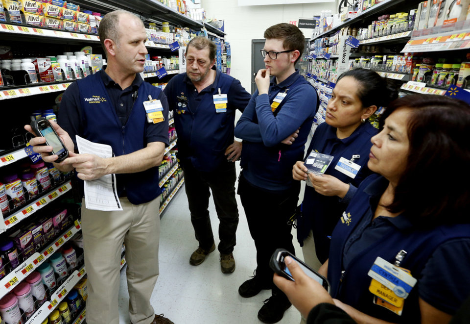 Photo -  Belle Isle Walmart trainer Kevin Early, far left, teaches a class to employees, from left, Lloyd Sanders, Andrew Holman, Regina Aguinaga and Cynthia Serbin. [Photo by Steve Sisney, The Oklahoman]