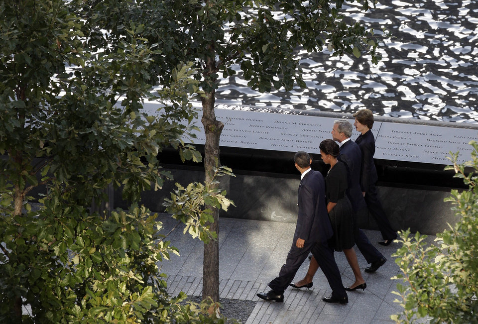 Photo -   President Barack Obama walks past a reflecting pool near the bronze-etched names of the victims of the terrorist attack 10 years ago with his wife Michelle, and former President George W. Bush and his wife, Laura, as they arrive for the ceremony marking the 10th anniversary of the attacks, Sunday, Sept. 11, 2011 in New York. Two reflecting pools built over the towers' footprints, part of a Sept. 11 memorial that was to open later in the day for relatives of the victims. (AP Photo/Mark Lennihan)