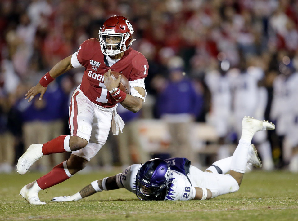 Photo - Oklahoma's Jalen Hurts (1) gets by TCU's Vernon Scott (26) in the fourth quarter during an NCAA football game between the University of Oklahoma Sooners (OU) and the TCU Horned Frogs at Gaylord Family-Oklahoma Memorial Stadium in Norman, Okla., Saturday, Nov. 23, 2019. OU won 28-24. [Sarah Phipps/The Oklahoman]
