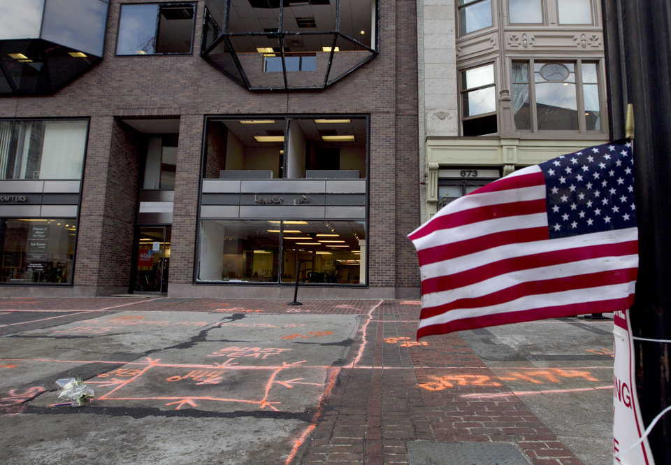 Photo - A flag flies at the blast site on Boylston Street between Dartmouth and Exeter Streets near the Boston Marathon finish line Monday, April 22, 2013 in Boston. Federal investigators formally released the finish line bombing crime scene to the city in a brief ceremony at 5 p.m. (AP Photo/Robert F. Bukaty)