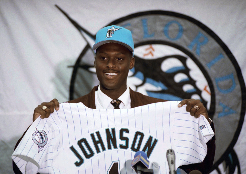 Photo - FILE - In this Nov. 10, 1992, file photo, former University of Maimi Hurricanes NCAA college baseball player Charles Johnson smiles as he holds his Florida Marlins uniform after signing to play for the Marlins. At least 16 former Hurricanes have taken advantage of the chance to return to complete their degrees, many of them baseball players, former Major League catcher Charles Johnson among them.  (AP Photo/Doug Jennings, File)