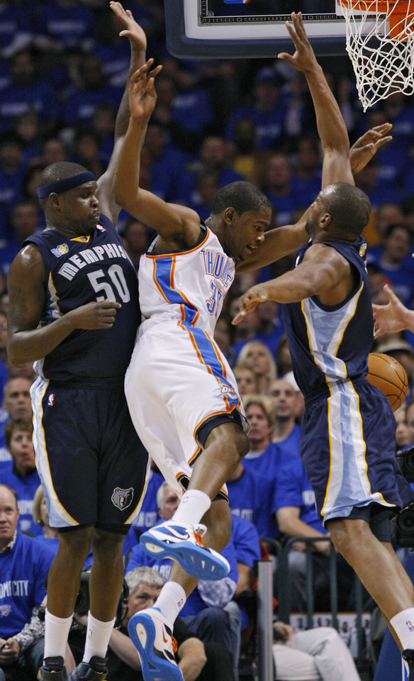 Photo - Kevin Durant (35) is defended on by Memphis' Zach Randolph (50) and Sam Young (4) during game one of the Western Conference semifinals between the Memphis Grizzlies and the Oklahoma City Thunder in the NBA basketball playoffs at Oklahoma City Arena in Oklahoma City, Sunday, May 1, 2011. Photo by Chris Landsberger, The Oklahoman