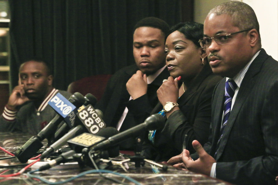Photo - Andre Santiago, far left, Basilio Santiago, second from left, and Cheryl Warner, second from right, the nephews and sister respectively of former Marine Jerome Murdough, listen as attorney Derek Sellsb speaks during a press conference on Friday May 16, 2014 in New York. Sells plans to file a wrongful death lawsuit against the city on behalf Murdough's family for his death, after he was found dead in a 100 degree cell on Rikers Island.  (AP Photo/Bebeto Matthews)