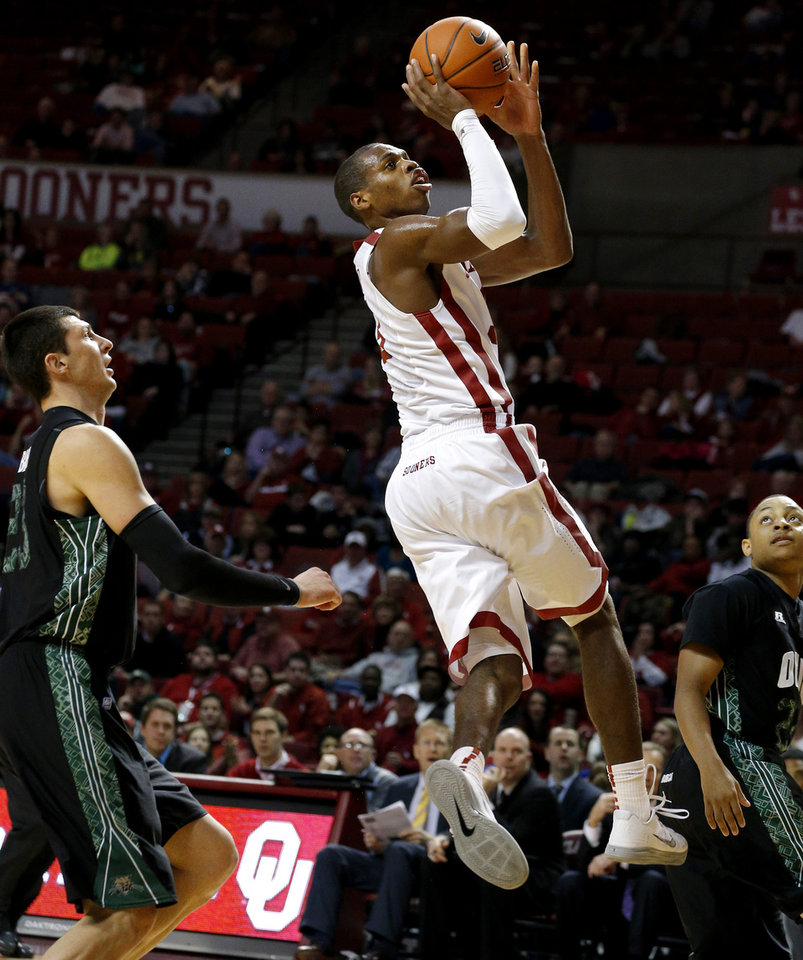 Photo - Oklahoma's Buddy Hield goes to the basket between Ohio's Ivo Baltic, left, and Ohio's Stevie Taylor during a NCAA college basketball game between the University of Oklahoma (OU) and Ohio at the Lloyd Noble Center in Norman, Saturday, Dec. 29, 2012. Oklahoma won 74-63. Photo by Bryan Terry, The Oklahoman