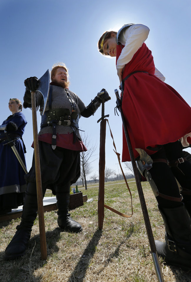 Photo -  David Thompson gives pointers on wearing weapons to Bethany Cavener during a Medieval Fair rehearsal in Reaves Park. The fair opens Friday and continues through Sunday. PHOTO BY STEVE SISNEY, THE OKLAHOMAN   STEVE SISNEY -