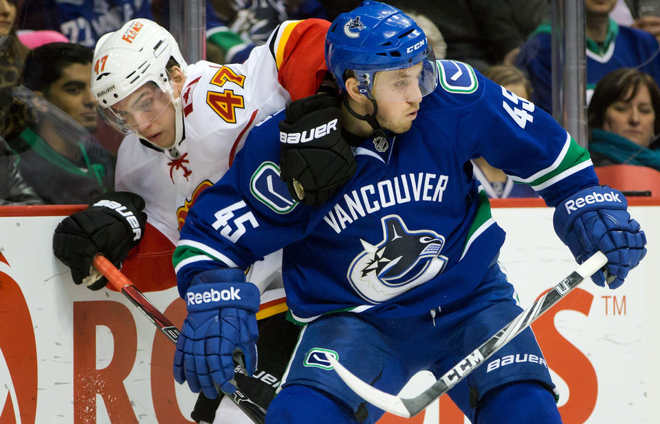 Vancouver Canucks' Jordan Schroeder, right, checks Calgary Flames' Sven Baertschi, of Switzerland, during the first period of an NHL hockey game game in Vancouver, British Columbia, on Wednesday, Jan. 23, 2013. (AP Photo/The Canadian Press, Darryl Dyck)