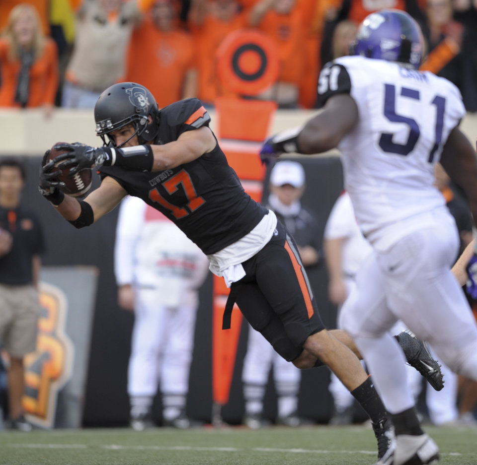Photo -   TCU linebacker Kenny Cain (51) watches as Oklahoma State receiver Charlie Moore (17) dives for a touchdown during the second half of an NCAA college football game in Stillwater, Okla., Saturday, Oct. 27, 2012. Oklahoma State defeated TCU 36-14. (AP Photo/Brody Schmidt)