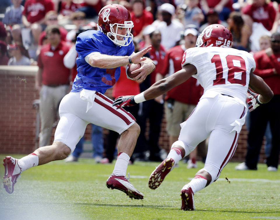 Quarterback Trevor Knight (9) tries to avoid Ahmad Thomas (18) during the annual Spring Football Game at Gaylord Family-Oklahoma Memorial Stadium in Norman, Okla., on Saturday, April 13, 2013. Photo by Steve Sisney, The Oklahoman