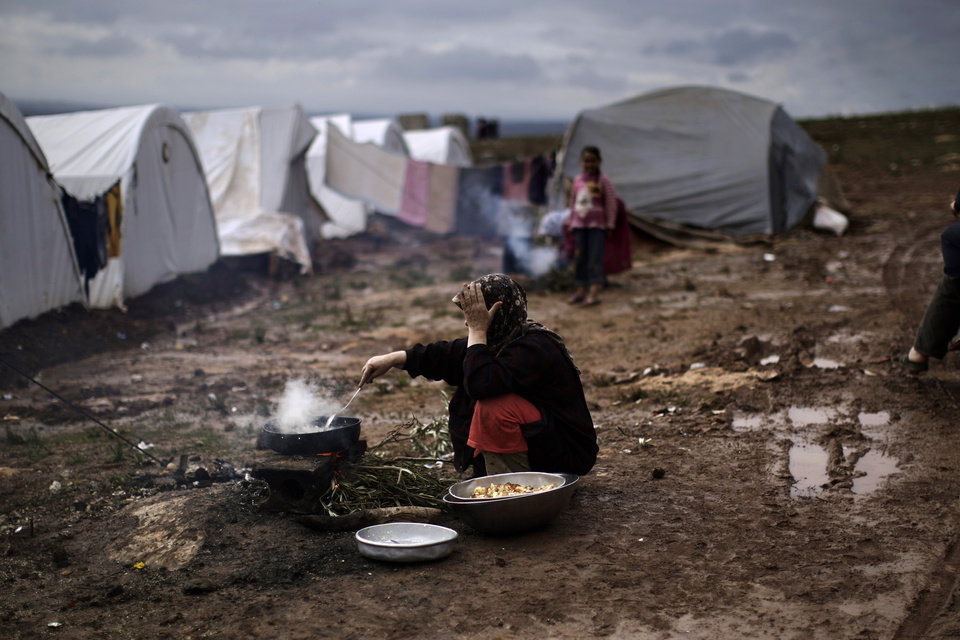 A Syrian woman who fled her home cooks for her family outside her tent at a camp for displaced Syrians in the village of Atmeh, Syria, Tuesday, Dec. 11, 2012. This tent camp sheltering some of the hundreds of thousands of Syrians uprooted by the country\'s brutal civil war has lost the race against winter: the ground under white tents is soaked in mud, rain water seeps into thin mattresses and volunteer doctors routinely run out of medicine for coughing, runny-nosed children. (AP Photo/Muhammed Muheisen) ORG XMIT: XMM515