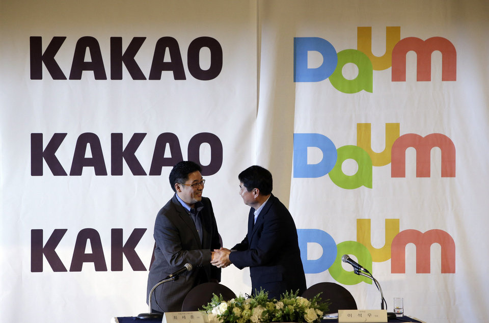 Photo - Daum Communications Corp. CEO Choi Sae-hoon, left, shakes hand with Kakao Corp. CEO Sirgoo Lee after their press conference in Seoul, South Korea, Monday, May 26, 2014. Mobile messenger service Kakao Talk is seeking a backdoor listing on the South Korean stock exchange by combining with the country's second largest Internet portal. (AP Photo/Lee Jin-man)