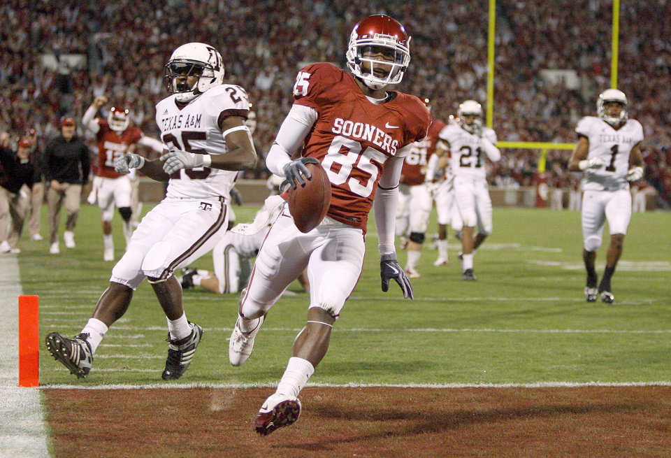 Photo - OU's Ryan Broyles scores a touchdown in front of Texas A&M's Jordan Pugh during the Big 12 college football game between the University of Oklahoma Sooners and the Texas A&M Aggies at Gaylord Family - Oklahoma Memorial Stadium in Norman, Okla., Saturday, November 14, 2009.  Photo by Bryan Terry, The Oklahoman