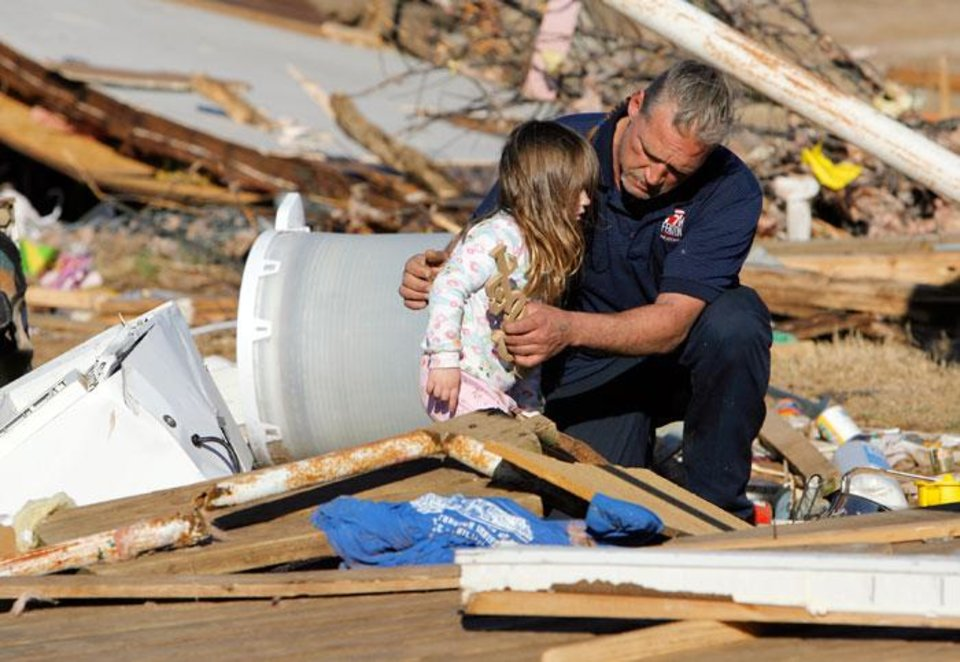 Photo -  Dennis Parker holds his granddaughter, Brooklyn Hickman, 3, while sifting through belongings from his destroyed mobile home at the Bar K Mobile Home Park in Lone Grove, Okla., Wednesday, February 11, 2009. On Tuesday, February 10, 2009, a tornado moved through Lone Grove killing at least nine people. BY NATE BILLINGS, THE OKLAHOMAN