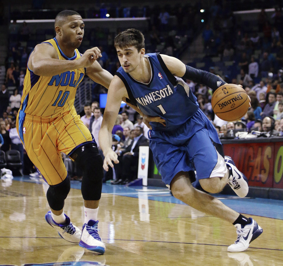 Photo - Minnesota Timberwolves guard Alexey Shved (1) drives past New Orleans Hornets guard Eric Gordon (10) in the first half of an NBA basketball game  in New Orleans, Friday, Jan. 11, 2013. (AP Photo/Bill Haber)