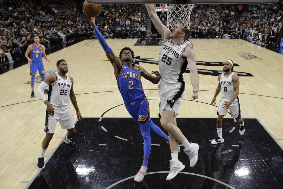 Photo - Oklahoma City Thunder guard Shai Gilgeous-Alexander (2) shoots past San Antonio Spurs center Jakob Poeltl (25) during the first half of an NBA basketball game, in San Antonio, Thursday, Jan. 2, 2020. (AP Photo/Eric Gay)