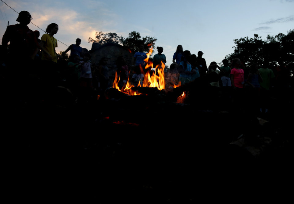 Photo -  Campers gather around a campfire where they are asked where they saw hope today.  [Photo by Kurt Steiss, The Oklahoman]