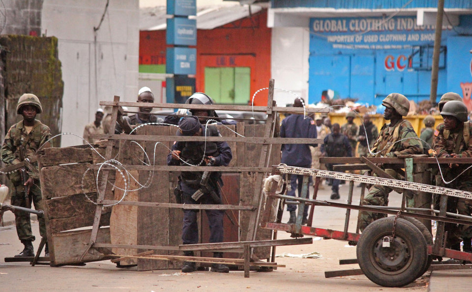 Photo - Liberia security forces, block a road near the West Point Ebola center as the government clamps down on the movement of people to prevent the spread of the Ebola virus in city Monrovia, Liberia, Wednesday, Aug. 20, 2014. Security forces deployed Wednesday to enforce a quarantine around a slum in the Liberian capital, stepping up the government's fight to stop the spread of Ebola and unnerving residents. (AP Photo/Abbas Dulleh)