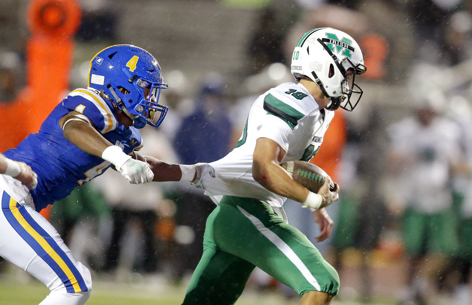 Photo - Piedmont's Decata Warrior tries to tackle Bishop McGuinness's Luke Tarman during the high school football game between Piedmont and Bishop McGuinness at Piedmont High School in Piedmont, Okla.,  Friday, Oct. 25, 2019. [Sarah Phipps/The Oklahoman]