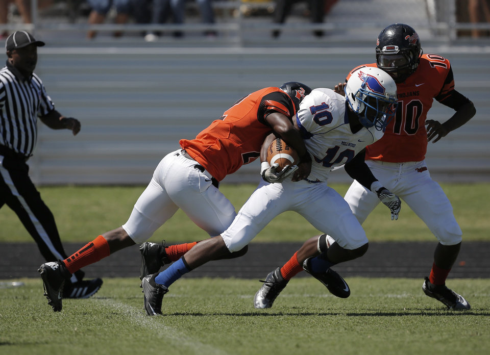 Douglass's Christopher High (22) takes down Millwood's Alfonso McMillan (10) during a high school football game between Douglass and Millwood in Oklahoma City, Saturday, Sept. 8, 2012.  Photo by Garett Fisbeck, The Oklahoman