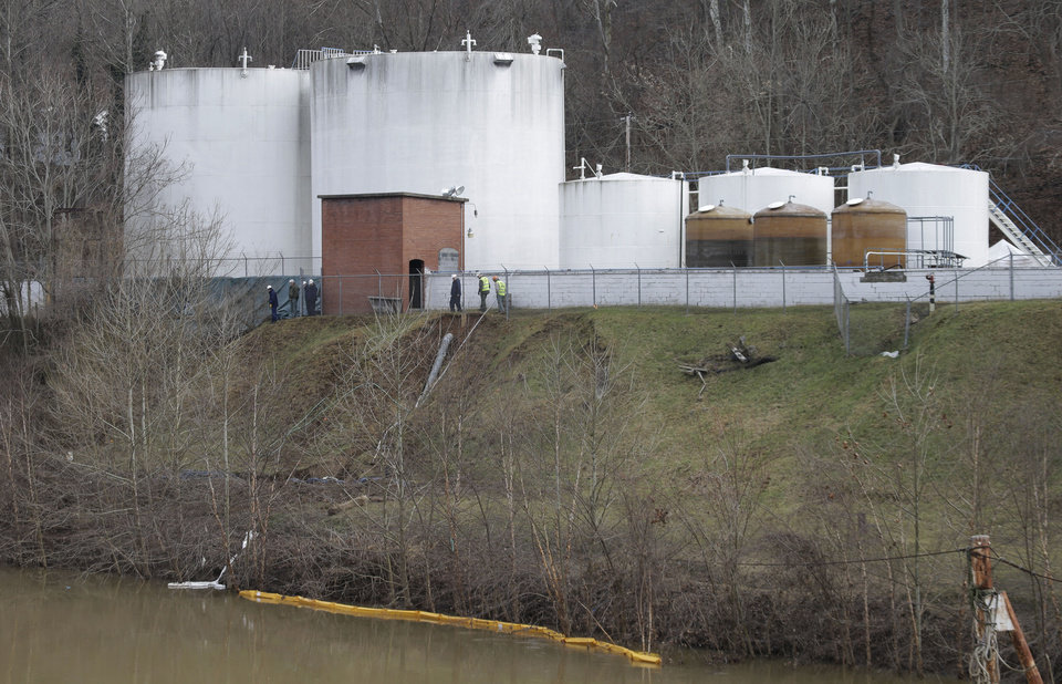 Photo - CORRECTS STATE TO W.VA. INSTEAD OF VA. - Workers inspect an area outside a retaining wall around storage tanks where a chemical leaked into the Elk River at Freedom Industries storage facility  in Charleston, W.Va., Monday, Jan. 13, 2014. The ban on tap water for parts of West Virginia was lifted on Monday, ending a crisis for a fraction of the 300,000 people who were told not to drink, wash or cook with water after the chemical spill tainted the water supply. Gov. Earl Tomblin made the announcement at a news conference, five days after people were told to use the water only to flush their toilets. (AP Photo/Steve Helber)
