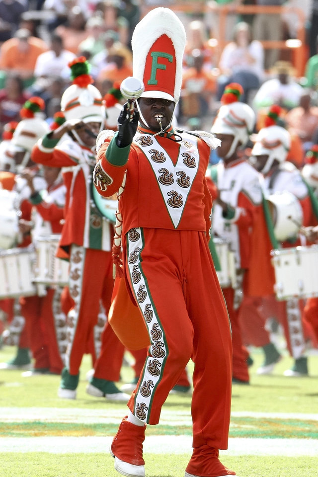Photo -   FILE -In this Oct. 8, 2011 file photo, Florida A&M Marching 100 Drum Major Robert Champion performs during a performance at halftime of the game against Howard University at Bragg Memorial Stadium in Tallahassee, Fla. Thirteen people were charged Wednesday, May 2, 2012, for their roles in the hazing death of Florida A&M university drum major who was severely beaten during a ritual, a prosecutor said. (AP Photo/Don Juan Moore)