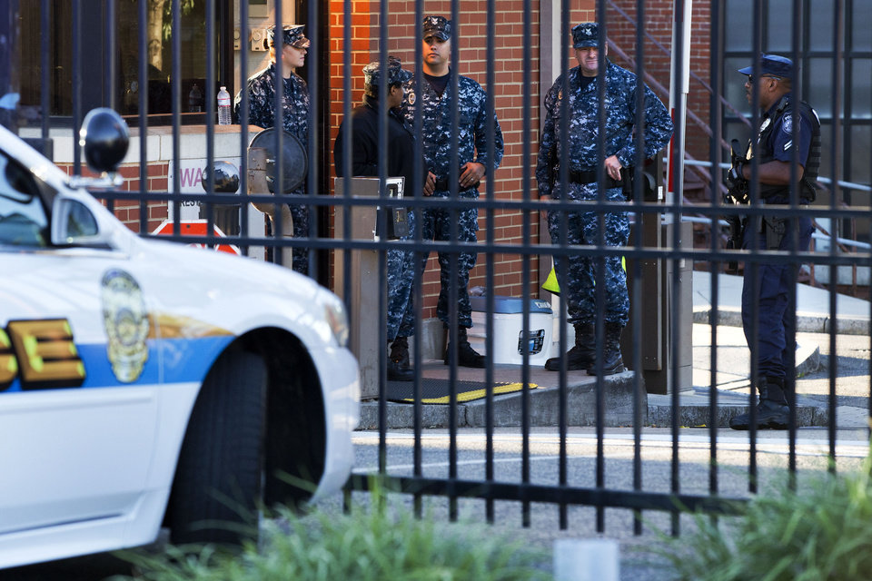 Photo - An officer who said he was with the Department of Defense, right, and members of the Navy, stand guard inside the gate of the closed Washington Navy Yard in Washington, on Tuesday, Sept. 17, 2013, the day after a gunman launched an attack inside the Washington Navy Yard on Monday, spraying gunfire on office workers in the cafeteria and in the hallways at the heavily secured military installation in the heart of the nation's capital. (AP Photo/Jacquelyn Martin)