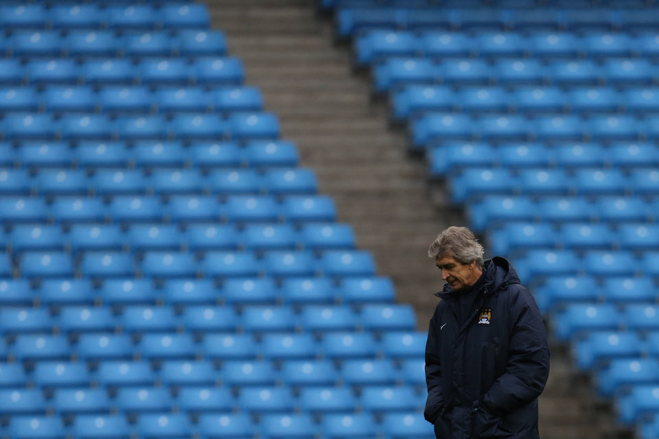 Photo - Manchester City's manager Manuel Pellegrini stands by as his team train at the Etihad Stadium, Manchester, England, Monday Feb. 17, 2014. Manchester City will play Barcelona on Tuesday in a Champions League first knock out round soccer match. (AP Photo/Jon Super)