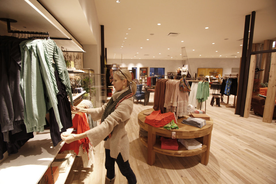 Photo - Linda Land organizes merchandise in the Anthropologie just before the store on Classen Curve opened earlier this year. photo by Steve Gooch, The Oklahoman Archives
