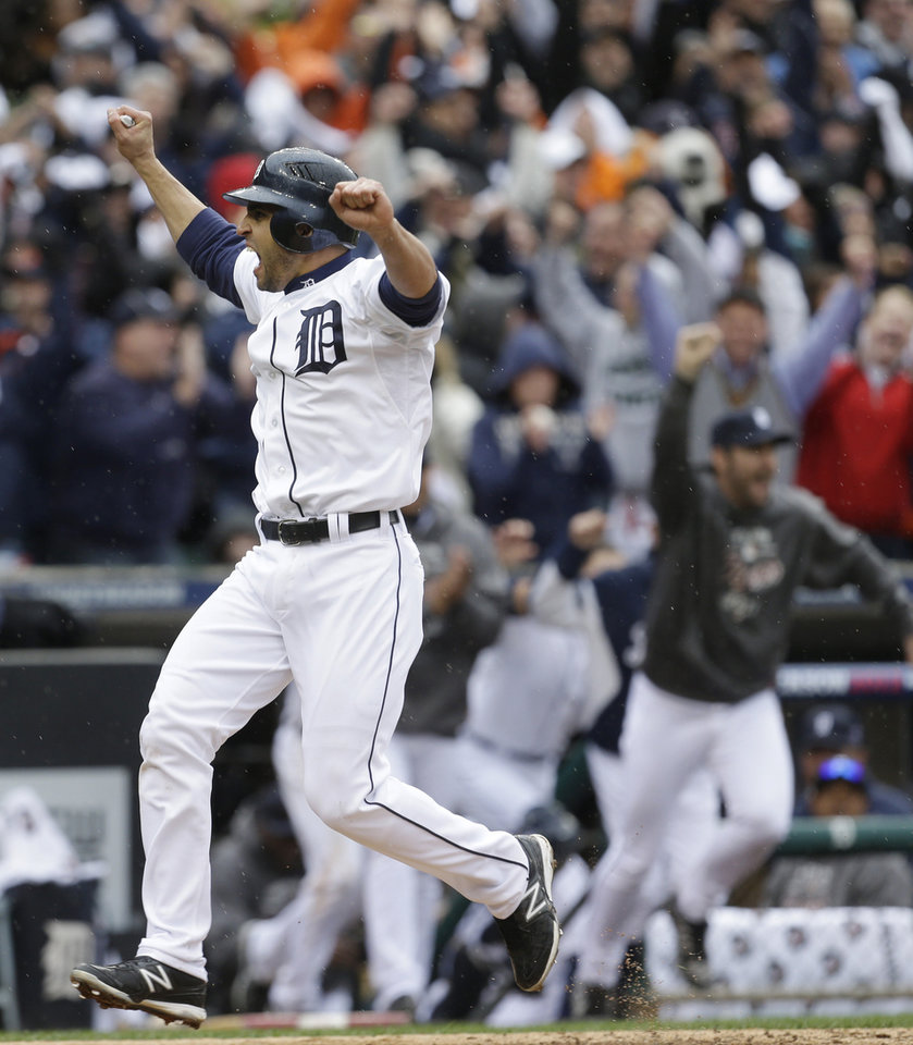 Photo -   Detroit Tigers' Omar Infante scores the winning run in the ninth inning on a sacrifice fly by teammate Don Kelly in Game 2 of the American League division baseball series, Sunday, Oct. 7, 2012, in Detroit. (AP Photo/Paul Sancya)