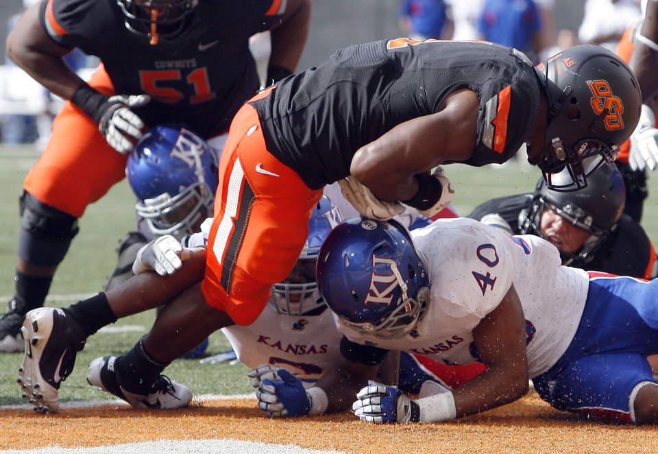 Photo - Oklahoma State's Joseph Randle (1) scores a touchdown as Kansas' Ray Mitchell (40) defends during the first half of the college football game between the Oklahoma State University Cowboys (OSU) and the University of Kansas Jayhawks (KU) at Boone Pickens Stadium in Stillwater, Okla., Saturday, Oct. 8, 2011. Photo by Sarah Phipps, The Oklahoman