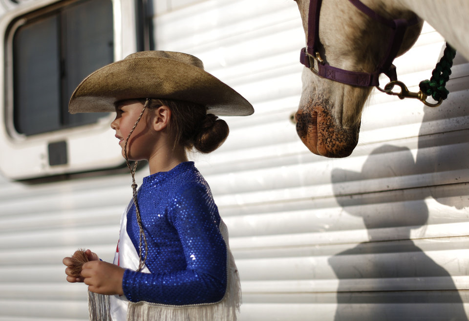 Edmond Round Up Club Junior  Princess Scout Payne, 6, of Okarche, gets ready beside her horse, Rio, for the annual LibertyFest Rodeo in Edmond. PHOTO BY BRYAN TERRY, THE OKLAHOMAN. <strong>Bryan Terry - THE OKLAHOMAN</strong>