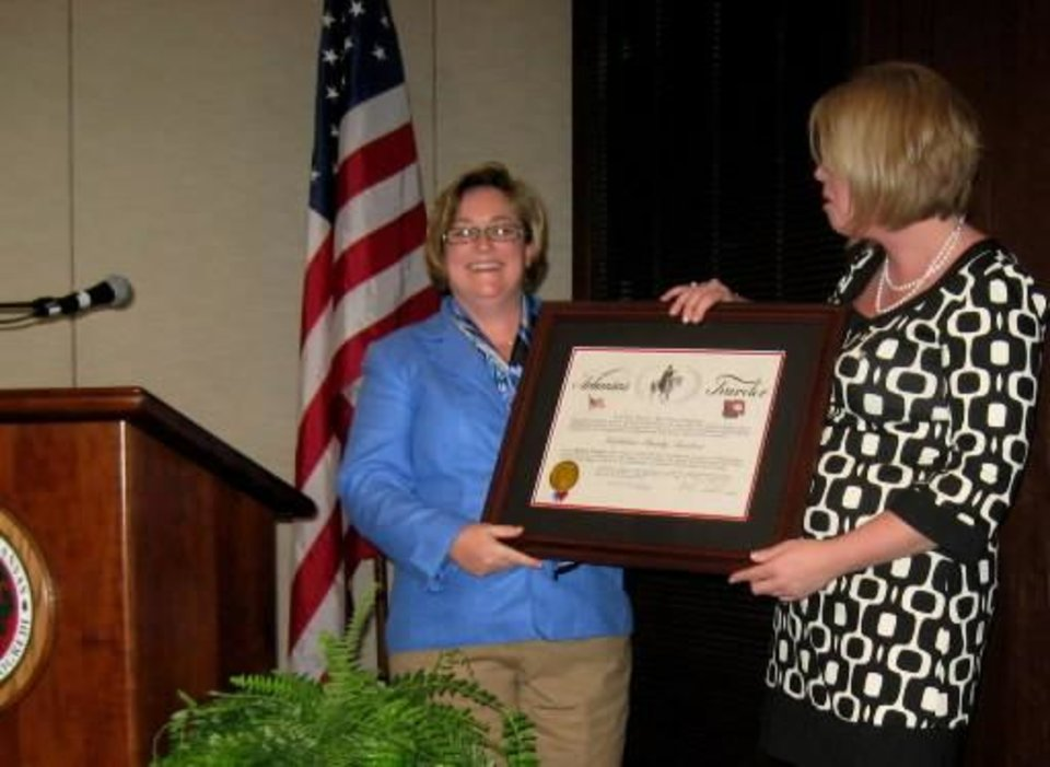 THE ARKANSAS TRAVELER....Ann Bordelon gives  Kate Stanton the  official governor's proclamation. 80 Delta Gammas were on hand for  the occasion as well as a surprise guest, Kate's mother, Flo Stanton,  Bedford, Tx. (Photo provided).